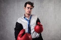 Fight young businessman fighting with boxing gloves Royalty Free Stock Photos