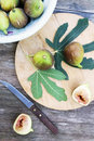 Figs with fig s leaves on the wooden board Royalty Free Stock Photography