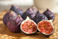 Figs fresh on wooden board one cut in half Stock Photos