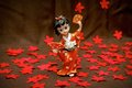 Figurine japanese geisha on a brown background and red flowers Stock Photography