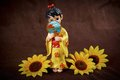 Figurine japanese geisha on a brown background and yellow flowers Stock Photos