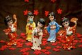 Figurine japanese geisha five on a brown background and red flowers Royalty Free Stock Photo