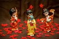 Figurine japanese geisha three on a brown background and red flowers Stock Photos