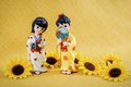 Figurine japanese geisha two on a yellow background and yellow flowers Royalty Free Stock Image