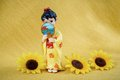 Figurine japanese geisha on a yellow background and yellow flowers Stock Photos