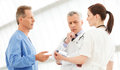 Figuring out the correct medication three doctors discussing th report standing close to each other Stock Image
