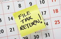 File tax return hand written reminder to on a yellow post it note stuck to a calendar background Stock Photos