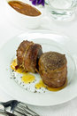 Filet mignon wrapped in bacon with sweet sauce Stock Images