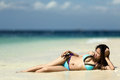 Filipina woman lying on sand the seashore Stock Photo