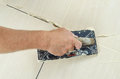 Fill the tile joints with grout hand of man holding a rubber float and filling Stock Photography