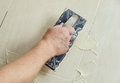 Fill the tile joints with grout hand of man holding a rubber float and filling Royalty Free Stock Photo
