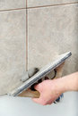 Fill the tile joints with grout hand of man holding a rubber float and filling Stock Images