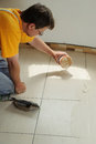 Fill the tile joints with grout worker pours from bucket on floor Royalty Free Stock Photo