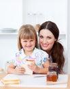 Fille mignonne et sa mère mangeant des parts de pain Photos stock
