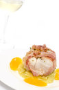Fillet from cod with bacon roasted on a white plate in vertical format Royalty Free Stock Photography