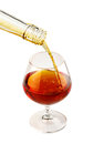 Filling a glass of brandy isolated on white Royalty Free Stock Images