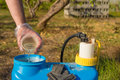 Filling in pesticide hand with plastic glove into a garden sprayer Royalty Free Stock Images