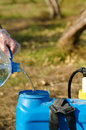 Filling a pesticide sprayer against the background of citrus orchard Royalty Free Stock Photo