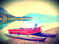 Film effect. Abandoned red gray fishing boat on bank of Alpine  lake. Autumnal morning at  lake  in gentle sunlight. Royalty Free Stock Photo