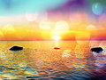 Film effect. Romantic morning at sea. Big boulders sticking out from smooth wavy sea. Pink horizon with first hot sun rays. Royalty Free Stock Photo