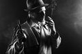 Film noir gangster smoking and holding a gun attractive in trench coat cigarette revolver Royalty Free Stock Images