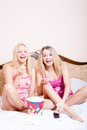 Film time: Two girl friends or sisters blond adorable attractive pretty young women sitting in bed with popcorn, watching movie Royalty Free Stock Photo
