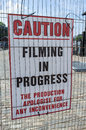 Filming in progress a sign warning people that is Royalty Free Stock Images