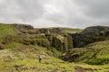 Fimmvorduhals trek in iceland trekker crossing green landscape during from skogar to porsmork passing eyjafjallajokull eruption Stock Photo