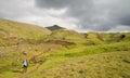 Fimmvorduhals trek in iceland trekker crossing green landscape during from skogar to porsmork passing eyjafjallajokull eruption Stock Image