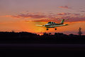Final approach trainer making a with a red sunset in the background while making a landing Royalty Free Stock Photography
