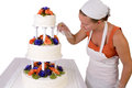Final touch ups on ruffled wedding cake baker lady with a white bandanna giving to a touchups has fondant ruffles the side and Royalty Free Stock Images