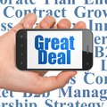 Finance concept: Hand Holding Smartphone with Great Deal on display Royalty Free Stock Photo