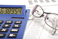 Finance report glasses and calculator on paper table with Royalty Free Stock Image