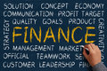 Finance word cloud is written on blue chalkboard by the hand of a businessman Royalty Free Stock Photography