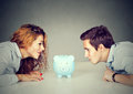 Finances in divorce concept. Wife and husband can not make settlement looking at piggy bank sitting at table looking at each other