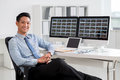 Financial analyst portrait of smiling vietnamese sitting at his workplace Stock Image