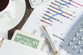 Financial analytics magnifing glass and documents with data lying on table Royalty Free Stock Photo