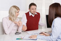 Financial business meeting young married couple adviser and c clients sitting at desk Royalty Free Stock Image