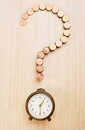 Financial decision question mark sign made out of coins and alarm clock Royalty Free Stock Photos