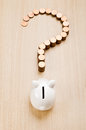 Financial decision question mark sign made out of coins in front of a piggy bank Stock Photography