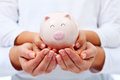 Financial education concept adult and child hands holding pigg smiling piggy bank Royalty Free Stock Photography