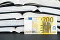 Financial knowledge euro banknote leaning on a stash of books for your advice business secrets accounting or copy Stock Images