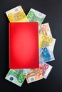 Financial knowledge euro banknotes sticking out of a book for your advice business secrets accounting or copy Stock Images