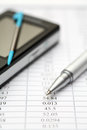 Financial statements ballpoint pen and pda with digitized pen on shallow depth of feild close up Royalty Free Stock Images