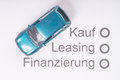 Financing a car model on sheet of paper with the german words buying leasing and Stock Photo