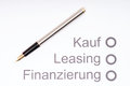 Financing a car pen on sheet of paper with the german words buying leasing and Royalty Free Stock Photo