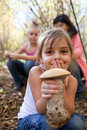 Find in the forest little girl holding mushroom with family background Royalty Free Stock Photos
