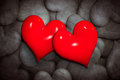 Find love concept. Two red hearts among many black and white ones.