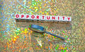 Finding a golden opportunity text inscribed in red uppercase letters on small white cubes with hand magnifier alongside and Stock Photography