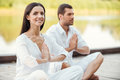 Finding peace and harmony inside themselves beautiful young couple in white clothing meditating outdoors together keeping eyes Royalty Free Stock Photo